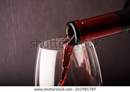 Wine glass and bottle on dark background - stock photo