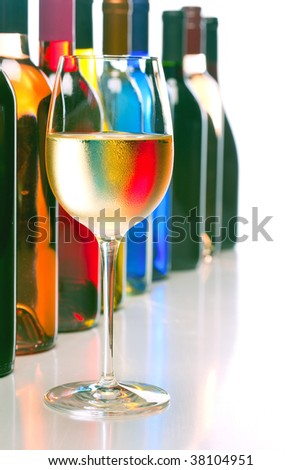 wine glass and bottles against white background