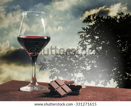 Wine glass and chocolate with cloudscape and tree silhouette - stock photo