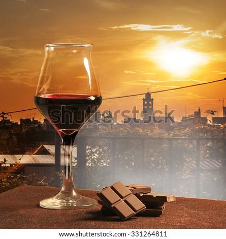 Wine glass and chocolate with orange city sunset - stock photo