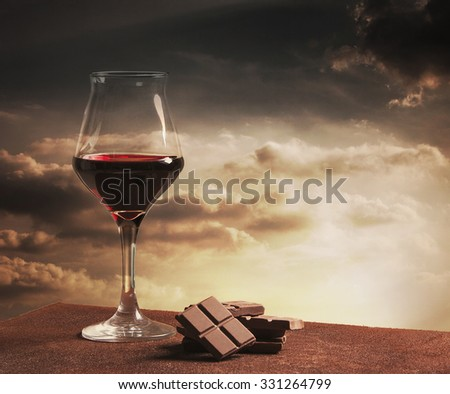 Wine glass and chocolate with orange sunset cloudscape - stock photo