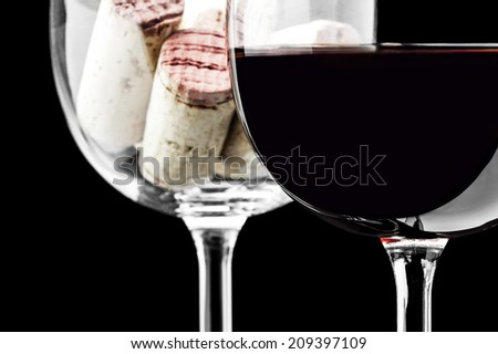 Wine glass and corks on a black background
