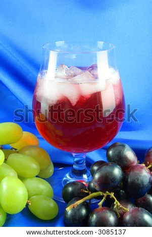 wine glass and grapes on a blue satin background