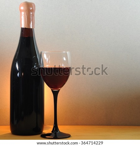 Wine glass and old prized bottle on a wooden table - stock photo
