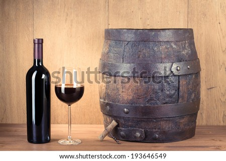 Wine glass, bottle, old wood barrel and corkscrew - stock photo