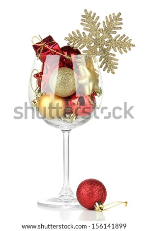 Wine glass filled with christmas decorations, isolated on white - stock photo