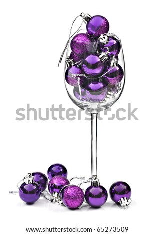 Wine glass filled with purple christmas decorations - stock photo