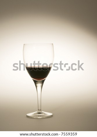 wine glass filled with red wine with special lighting - stock photo