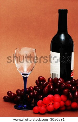 Wine glass, grapes and bottle on  biege background - stock photo