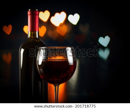 wine glass near bottle on hearts bokeh background, concept of valentine's day - stock photo