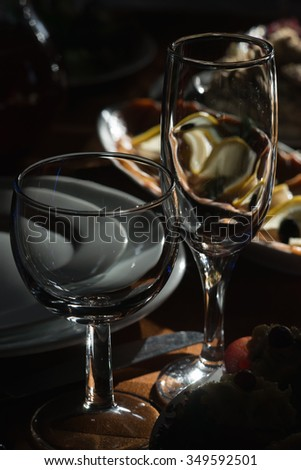 Wine glass on table in restaurant, Darkness light, food on background - stock photo