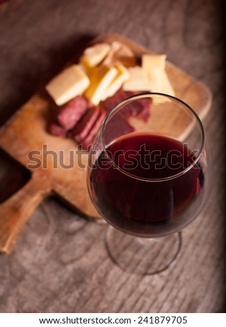 wine glass on wooden table , tasty cheese and salamy in background  - stock photo