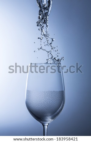 Wine glass splash splatter rinse clean with condensation drops on blue gradient background - stock photo