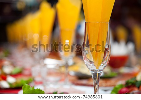 Wine glass with a napkin in the Inside on the background of the banquet table - stock photo