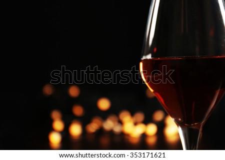 Wine glass with bokeh on dark background - stock photo