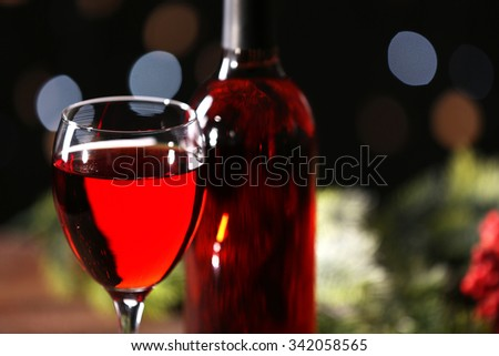 Wine glass with bottle on blurred background, close up