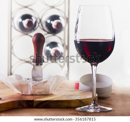 Wine glass with bottles and cheese. Selective focus