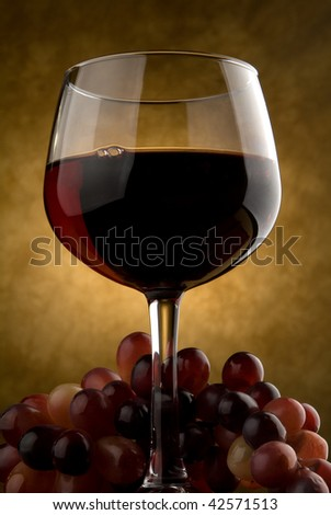 Wine glass with red wine and grapes - stock photo