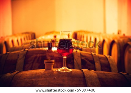 Wine glass with red wine on a cask in cellar - stock photo