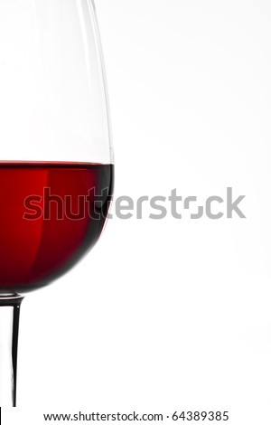Wine glass with red wine over plain white backdrop