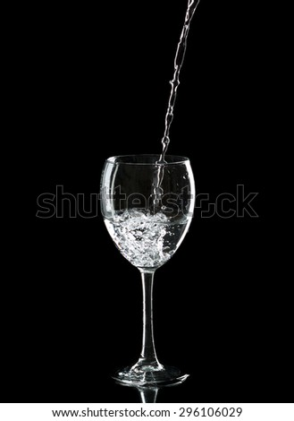 Wine glass with water over black background - stock photo