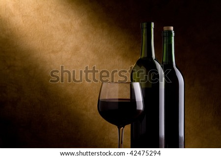 wine glass with wine and two wine bottles