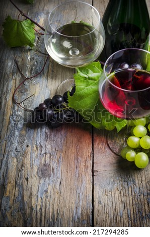 Wine glasses and grape on rustic wooden table - stock photo