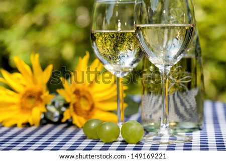 Wine glasses and sunflowers in the background - stock photo