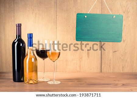 Wine glasses, bottles, sign board blank - stock photo