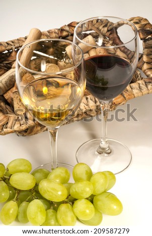 Wine glasses, corks and grapes on white background - stock photo