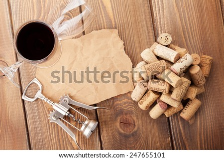 Wine glasses, corks, corkscrew and piece of paper for copy space over rustic wooden table background. Top view - stock photo