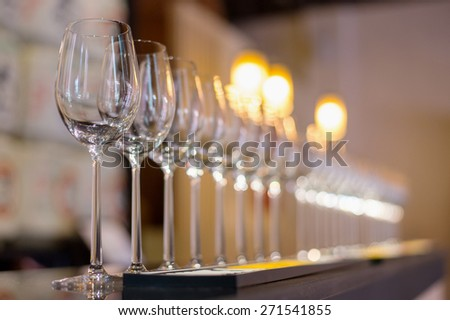 Wine glasses in row on bar - stock photo