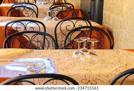 Wine glasses on the tables of street cafes - stock photo