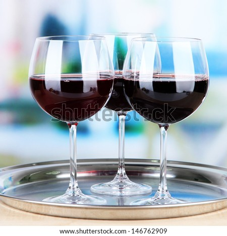 Wine glasses on  tray, on bright background - stock photo