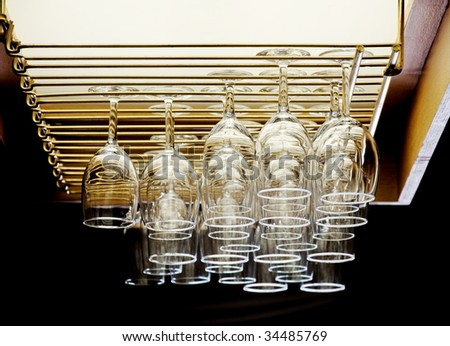 Wine glasses place on the rack of a bar