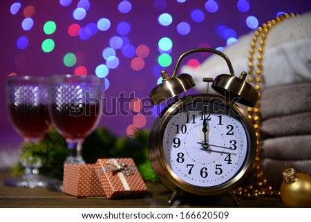 Wine glasses, retro alarm clock and Christmas decoration on bright background