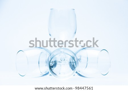Wine glasses stand and lie symmetrically on white - stock photo