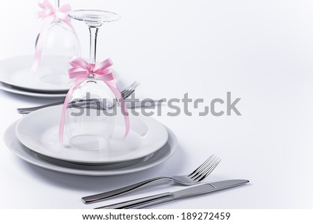 Wine glasses turned upside down with pink decoration as background for invitation and menu - stock photo