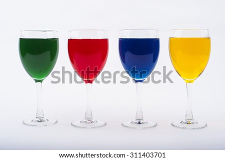 Wine Glasses with Brightly Colored Water on a White Background - Red, Blue, Green, Yellow