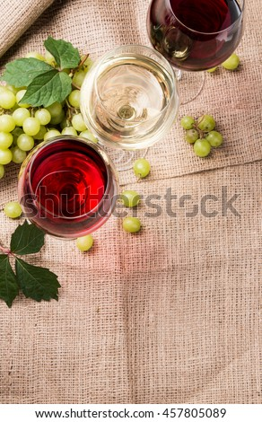 Wine glasses with red, white and rose. Cheese on nature background with fresh grapes  - stock photo