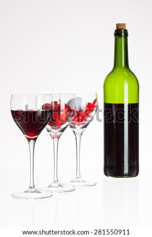 Wine glasses with red wine, heart and golf ball on white table