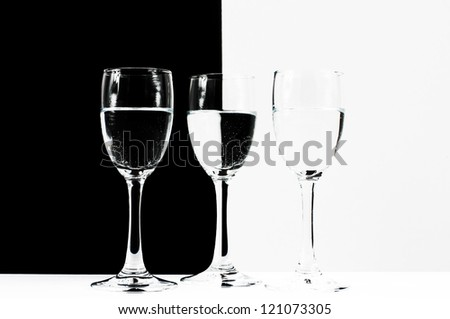 Wine glasses with white and black background reflection - stock photo