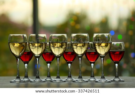 Wine glasses with wine on a table outside - stock photo
