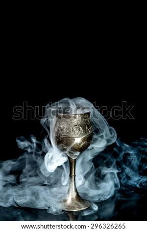Wine goblet with smoke on black background - stock photo