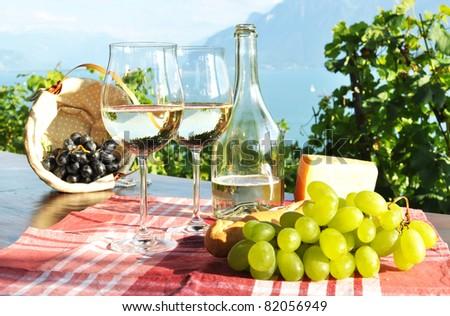 Wine, grapes and cheese against Geneva lake. Lavaux region, Switzerland - stock photo