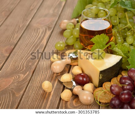 Wine, grapes and cheese on brown background