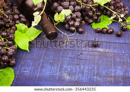 Wine grapes and wine on a wooden background - stock photo
