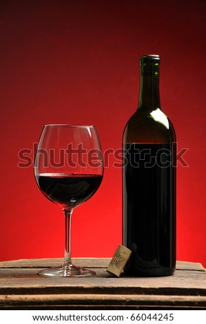 Wine in a glass next to a bottle - stock photo