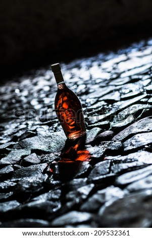 Wine in bottle on the stone floor in the dark grunge in wine cellar. Atmospheric shot with low depth of field. - stock photo