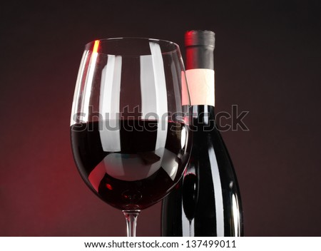Wine in glass and wine bottle close-up on dark background - stock photo